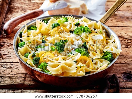 Metal frying pan full of freshly cooked savory broccoli bow tie pasta and lemon slices on worn out wooden table