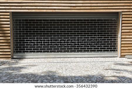 Metal garage doors embedded in the wooden wall. - stock photo