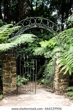 Metal Garden Gate With Arch Set In Brick Fence With Ferns And Trees