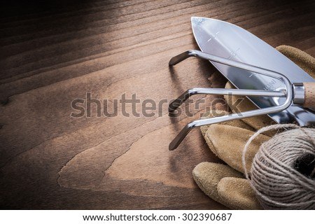 Metal gardening hand shovel rake brown leather safety gloves and hank of string on vintage wood board agriculture concept.