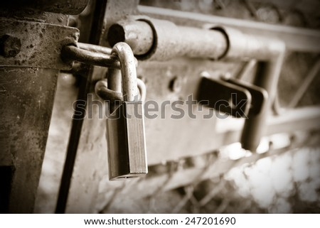 Metal gate closed with padlock - concept image with copy space - stock photo