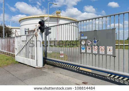 metal gate in front of an area with oil storage tanks in Amsterdam harbor - stock photo