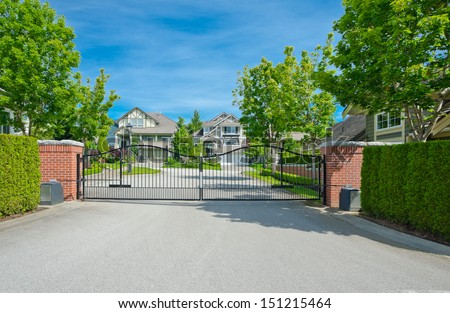 Metal gates with some residential houses behind in a nice and quiet neighborhood in the suburbs of Vancouver, Canada. - stock photo