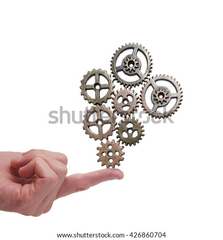 Metal gears balancing on a finger isolated on white