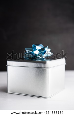 Metal gift box on white and black wooden backgrounds. Merry christmas card. Winter holidays. Xmas theme. Happy New Year. - stock photo