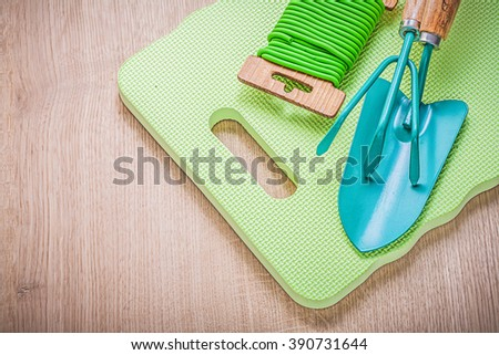 Metal hand spade rake garden tie wire foam kneeling pad on wooden board agriculture concept. - stock photo