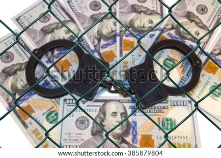 Metal handcuffs on the background of dollars under wire netting (lattice) - stock photo