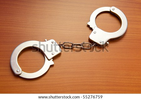 Metal handcuffs on the wooden background - stock photo