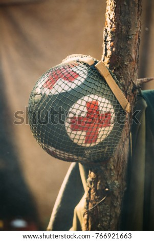 Metal Helmet Of United States Army Infantry Medic Soldier At World War II. Helmet Hanging On Tree Trunk In Forest Camp.