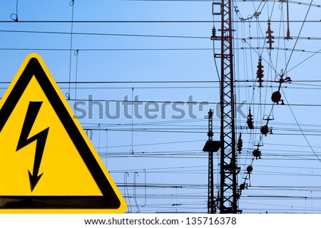 Metal high voltage danger sign and railway electric overhead contact wire all over. - stock photo