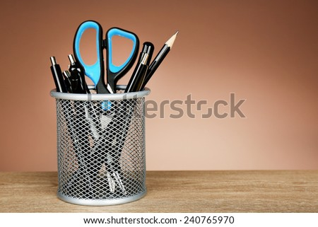 Metal holder with pens, pencil and scissor on wooden table and shaded color background - stock photo