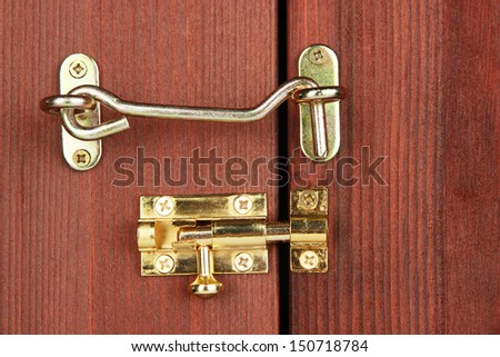 Metal hook and deadbolt in wooden door close-up - stock photo