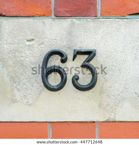 Metal house number sixty three. - stock photo