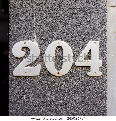 metal house number two hundred and four - stock photo