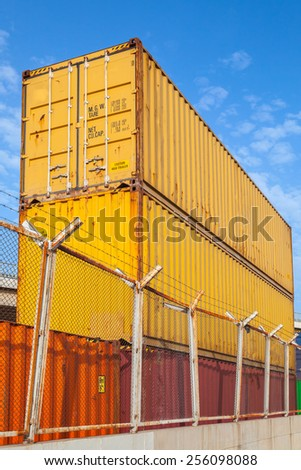 Metal industrial cargo containers are stacked under blue cloudy sky. Vertical photo - stock photo