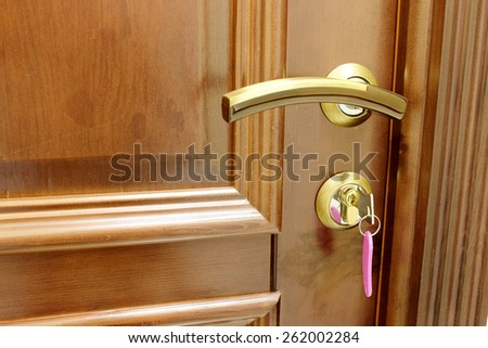 Metal key and keyring hanging from door lock  - stock photo