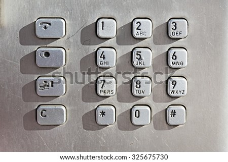 metal keypad buttons on a public phone box - stock photo