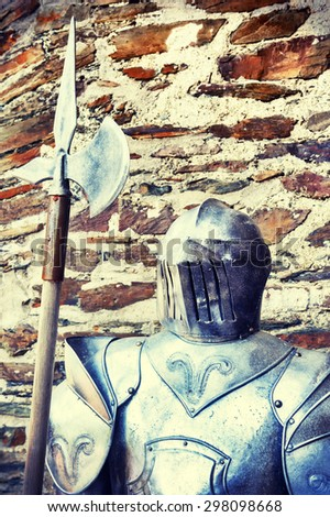 Metal knights armor on ancient stone wall background  - stock photo