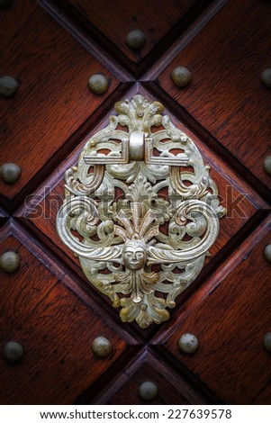 Metal knocker in the form of figures - stock photo