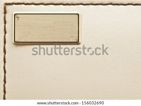metal label on old leather background  - stock photo
