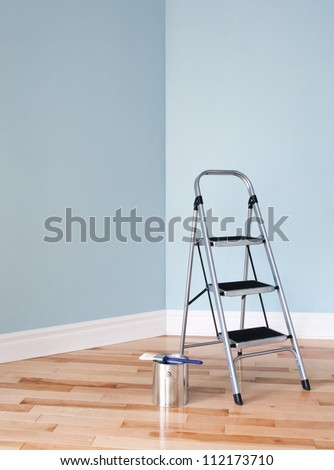 Metal ladder and a can of paint in empty room. Renovation project. - stock photo