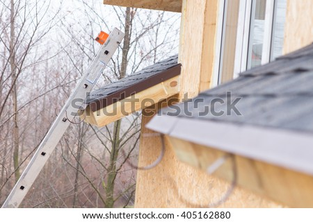 Metal ladder leaning against a tiled roof on a new build timber house giving access for roofers - stock photo