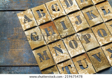 Metal lettering over a weathered wood background showing letters of the alphabet. - stock photo