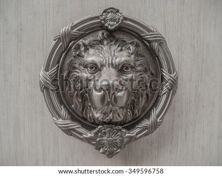 Metal lion head carving on marble slab.