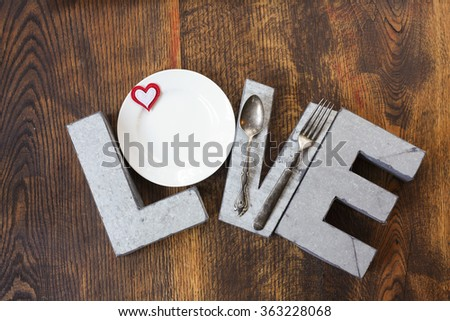 Metal love sign on wood background with plates - stock photo
