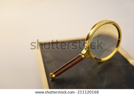 Metal magnifying glass standing on  wooden black board with beam of light. - stock photo
