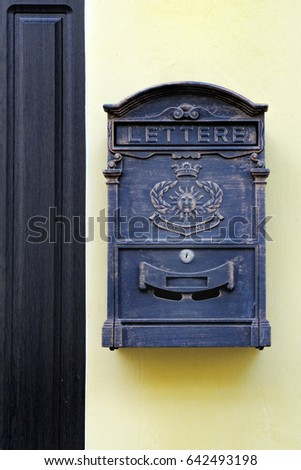 Elegant Metal Mailbox In Antique Style Hanging Near The Front Door Of The House On  Yellow Wall