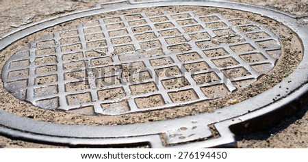 Metal manhole cover with checkered surface. Close up.  - stock photo