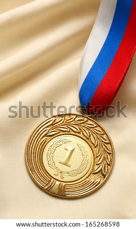 Metal medal on silk wrinkled cloth - stock photo