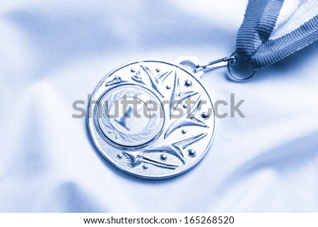 Metal medal on silk wrinkled cloth in toning - stock photo
