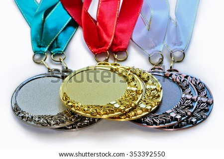 Metal medals for the first second and third place with ribbons of green red and white colours lies one on another isolated on white background - stock photo