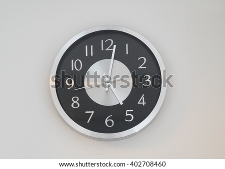 metal modern clock on white wall - stock photo