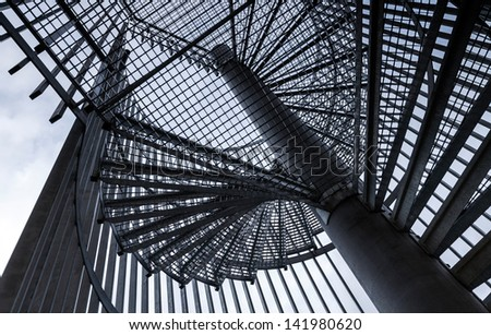 Metal modern spiral staircase details above blue sky - stock photo