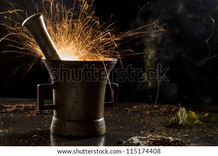 metal mortar with sparkling fire, surrounded with spices