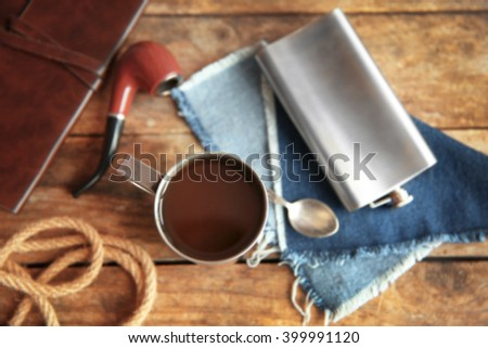 Metal mug of coffee with flask, spoon and tobacco pipe on wooden background