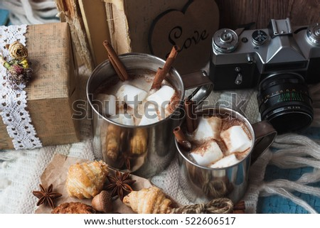 Metal mugs with cacao and marshmallows, with different decorations, soft focus background
