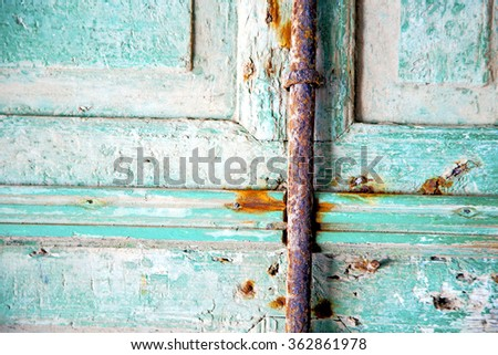metal nail dirty     stripped paint in the brown   red wood door and rusty  knocker - stock photo