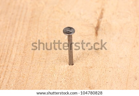 Metal nail in wooden plank - stock photo