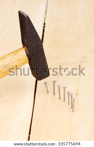 Metal nails in wooden plank and hammer - stock photo