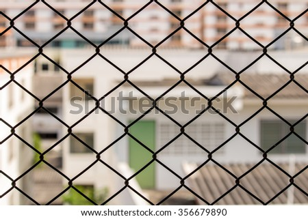 metal net with building blurred background,out of focus