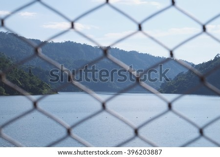 Metal net with the ocean background.
