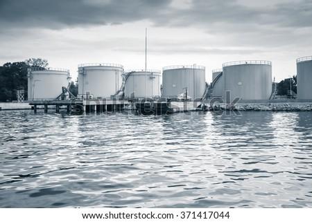 Metal oil tanks on the sea coast in Varna port, Bulgaria. Blue toned photo - stock photo