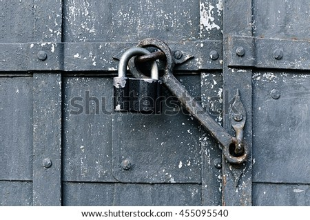 Metal old worn padlock with old door heck at the iron rusty door. Focus at the padlock and heck. - stock photo