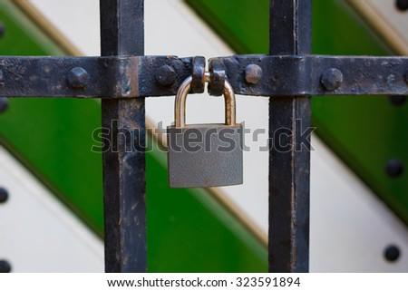 Metal padlock locking metal gate of a fortress in Poland. - stock photo