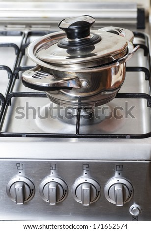 Metal pan on the gas stove in the kitchen - stock photo