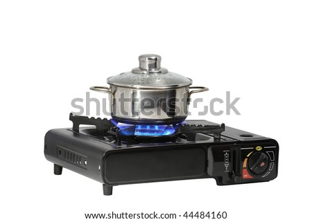 Metal pan standing on modern portable gas range with flame. Isolated on white background with clipping path - stock photo